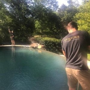 A Liquidus Pools pro skims a pool surface during weekly maintenance