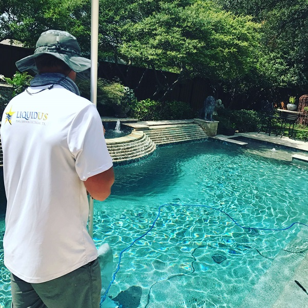 During Pool Cleaning, a Tech gets the last bits of debris out of the pool
