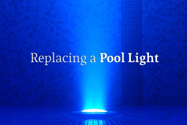 "A light shining at the bottom of a pool, lighting up the words ""Replacing a Pool Light"""