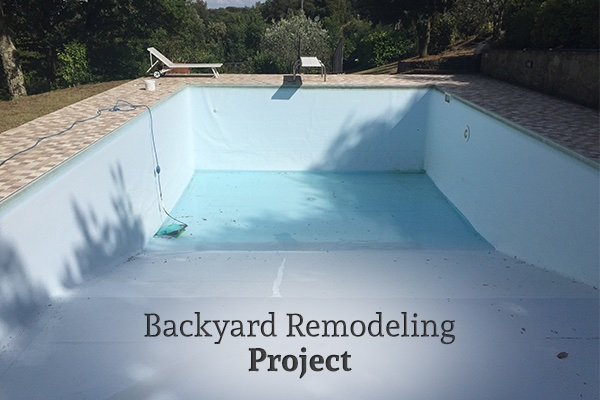 A look into a pool remodel, the pool is currently empty, with the words, backyard remodeling project.