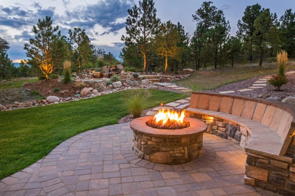 A fire pit is set on a concrete patio with a waterfall in the background.