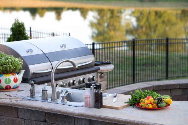 A beautiful shot of an outdoor kitchen with a grill.