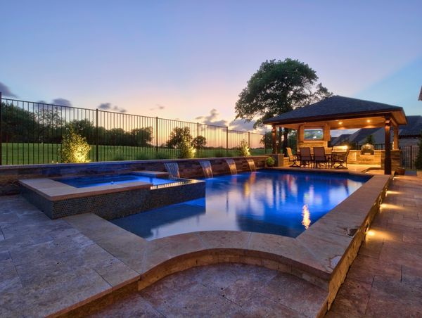 Beautiful well-lit custom backyard pool at sunset