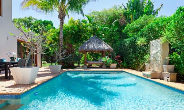 A beautiful backyard design featuring a pool and a tiki hut.
