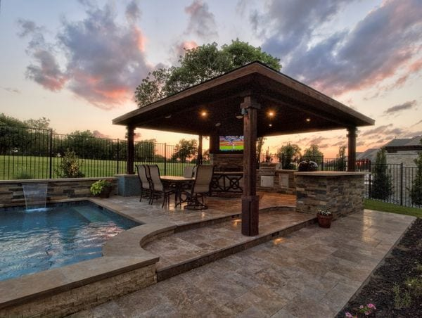 A gorgeous outdoor pool and kitchen area in sunset.