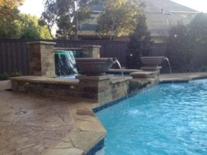 A gorgeous fountain next to an outdoor pool.