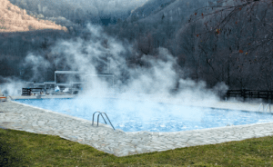 A heated pool with steam coming off the water.