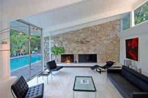 A gorgeous stone fireplace near an outdoor pool.